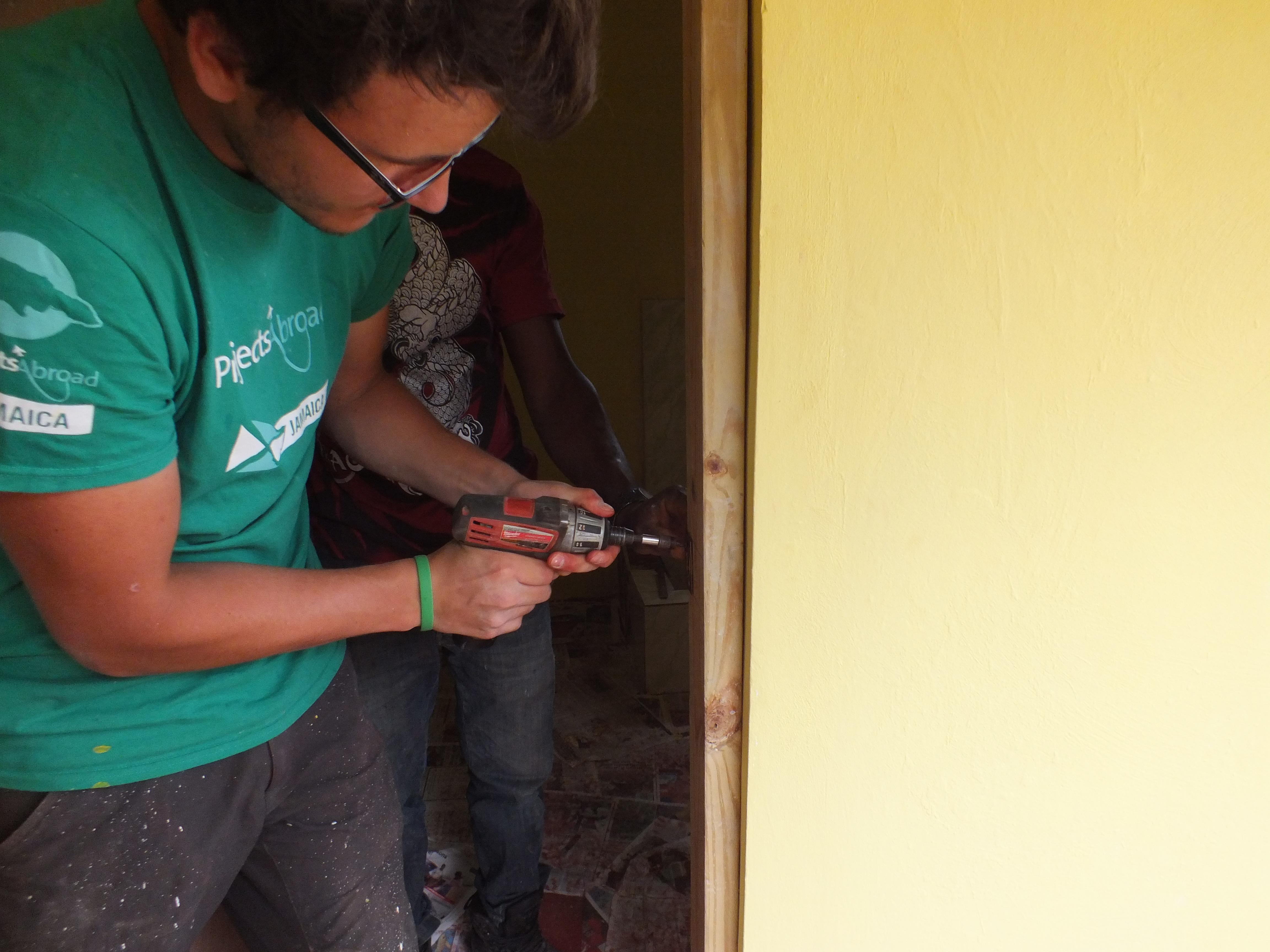 A volunteer helps with building a bathroom as part of construction volunteering in Jamaica for a group.